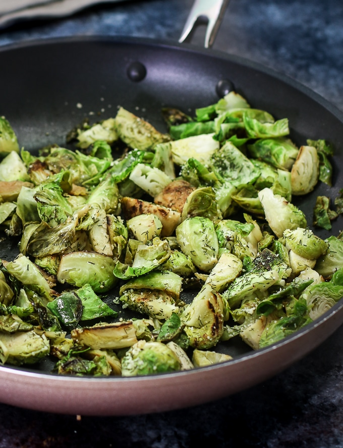 Sauteed brussels sprouts in a pan with parmesan and dill